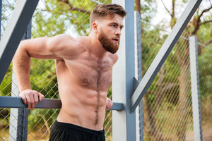 Young concentrated bearded strong man doing sports exercises outdoors