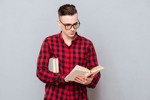 Young concentrated Man in glasses reading book in studio. Isolated gray background