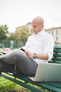 Young contemporary business man sitting on a bench in a city park, using notebook, writing on his agenda - business, planning, appointment concept