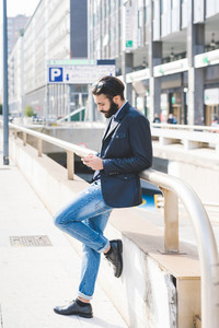young contemporary businessman leaning on wall outdoor in the city holding a smartphone - technology, social network, communication concept