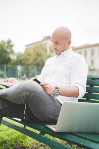 Young contemporary businessman remote working sitting on a bench outdoor in a city wiritng on her agenda - organizing, small business, remote working