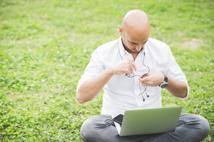 Young contemporary businessman remote working sitting outdoor in a city park using computer and earphones - portability, small business, business call concept