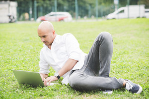 Young contemporary businessman remote working sitting outdoor in a city park using computer - portability, small business, networking concept