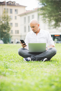 Young contemporary businessman remote working sitting outdoor in a city park using smart phone and computer - portability, small business, networking concept
