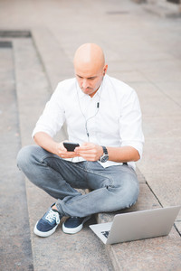 Young contemporary businessman remote working sitting outdoor in the city using smart phone and computer - portability, small business, networking concept