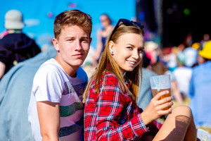 Young couple at summer music festival, drinking beer, sitting on the grass in front of stage, rear, viewpoint