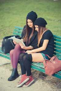 young couple beautiful women girls autumn using tablet outdoor