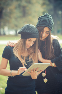 young couple beautiful women girls autumn using tablet outdoor