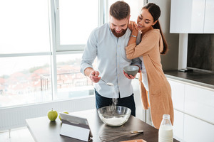 Young couple cooked in kitchen with tablet