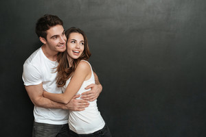 Young couple cuddling in studio and looking away. Isolated dark background