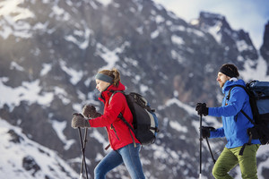 Young couple hiking outside in sunny winter mountains