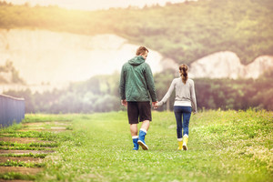 Young couple in colorful wellies walking in muddy nature.