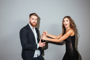 Young couple in formal wear fighting for champagne bottle over gray background