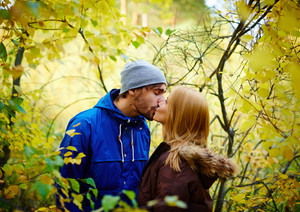 Young couple in love among autumn woods