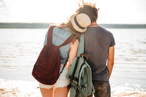 Young couple in love standing backwards hugging and looking at the seaside