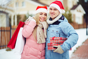 Young couple in Santa Claus hats holding gifts