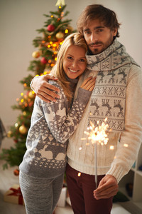 Young couple in stylish sweaters celebrating xmas at home