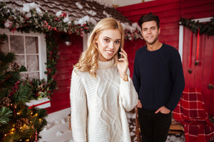 Young couple in sweaters near the red house. man on background