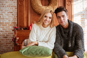 Young couple in sweaters near the sofa looks at camera