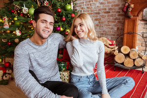 Young couple in sweaters sitting on the floor near the fir-tree. man looking at camera. girl looking at man