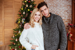 Young couple in sweaters standing near the fir-tree