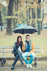 young couple in the park during autumn season outdoor - lovers valentine under umbrella sitting in a bench