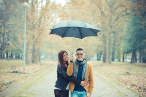 young couple in the park during autumn season outdoor - lovers valentine under umbrella