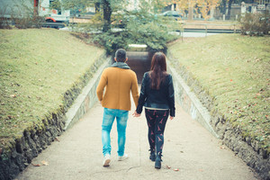 young couple in the park during autumn season outdoor - lovers valentine walking back hand to hand