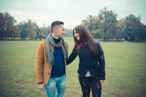 young couple in the park during autumn season outdoor - lovers valentine walknig hand to hand