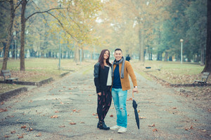 young couple in the park during autumn season outdoor - lovers valentine