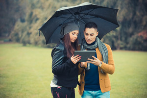 young couple in the park during autumn season outdoor - using tablet technological device during raining under umbrella