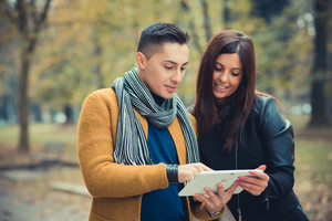 young couple in the park during autumn season outdoor - using tablet technological device