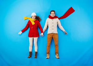 Young couple in winter clothes on blue background