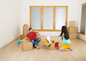 Young couple is moving into new house with lot of boxes. Woman is pregnant.
