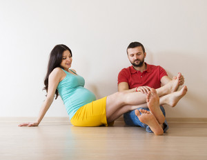 Young couple is sitting on the floor in their empty new house. Woman is pregnant.