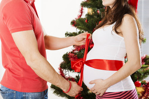 Young couple is standing close to christmas tree. Woman is pregnant and tied with red ribbon.