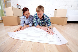 Young couple lying on the floor and looking at blueprint of new house