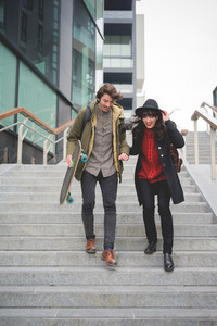 Young couple of caucasian woman and man, with skate and moustache, walking down the stairs hugging and smiling - youth, carefree, freshness concept