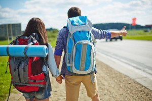 Young couple of travelers with rucksacks hitch-hiking by road