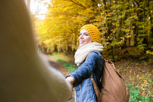Young couple on a walk in colorful autumn forest. Unrecognizable man holding hand of beautiful woman.