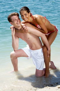 Young couple posing at the beach during vacation and looking at camera