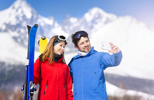 Young couple skiing outside in sunny winter mountains