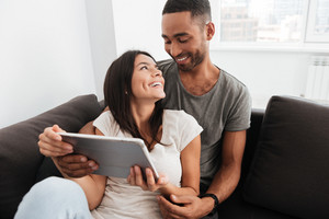 Young couple smile together while using tablet computer, sitting on sofa indoor. Look at each other.