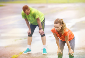 Young couple stretching after the run on asphalt in rainy weather