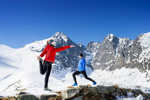 Young couple stretching before jogging outside in sunny winter mountains
