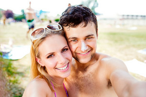 Young couple sunbathing, taking selfie. Sunscreen on the nose. Summer heat. Woman with sunglasses in bikini.
