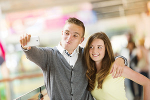 Young couple taking selfie with a cellphone in a shopping mall