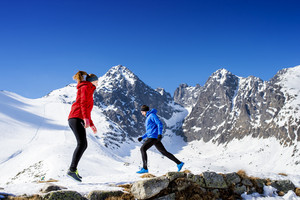 Young couple warming up before jogging outside in sunny winter mountains