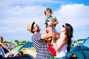 Young couple with their baby daughter between tents at summer music festival