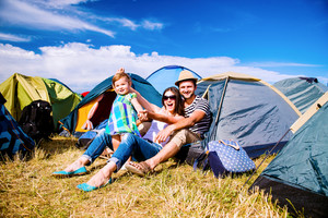 Young couple with their baby daughter in a tent at summer music festival